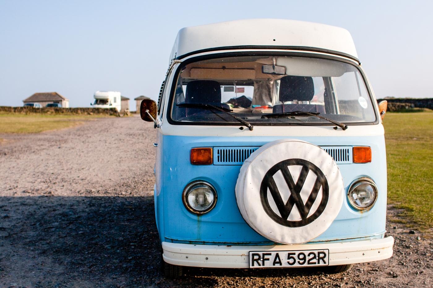 A light blue VW camper van parked in a carpark