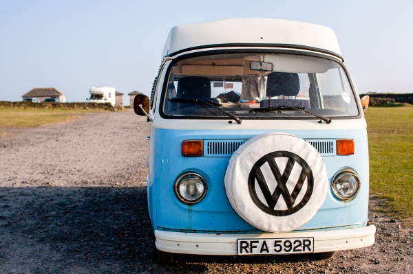 A light blue VW camper van parked in a carpark